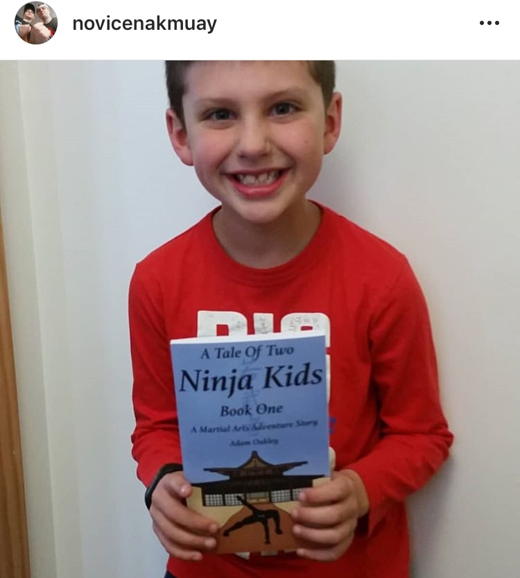 Ninja kid holding ninja kids book - A Tale Of Two Ninja Kids - A Martial Arts Adventure Story Book.